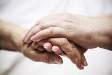 Elderly woman's hand being held by another person's hand