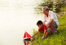 Elderly man playing with grandson by the water.