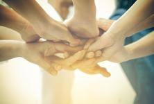 people putting there hands together to show teamwork
